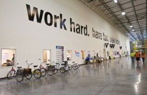 "Amazon's 'Work Hard. Have Fun. Make History"" motto in large print on one of their warehouse walls."